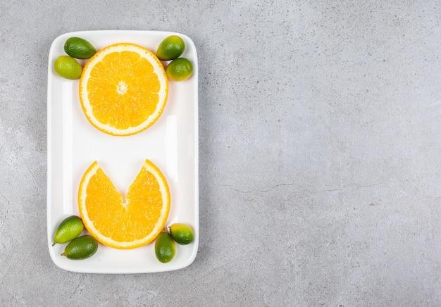 Bovenaanzicht van stukjes sinaasappel met kumquats op witte plaat.