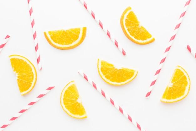 Bovenaanzicht van stukjes sinaasappel met rietjes voor sap