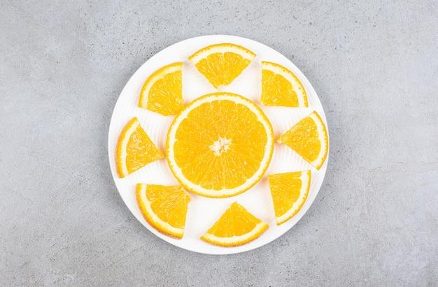 Bovenaanzicht van stukjes sinaasappel op een witte plaat.