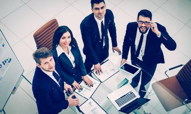 Bovenaanzicht van succesvol business team bereidt zich voor op de presentatie van een nieuw financieel project van het bedrijf. de foto heeft een lege ruimte voor uw tekst.