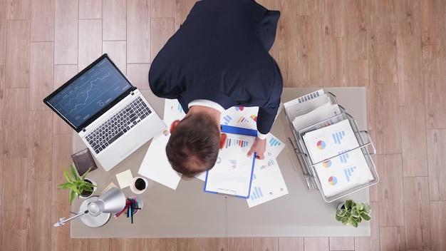 Bovenaanzicht van succesvolle zakenman die financiële documenten analyseert