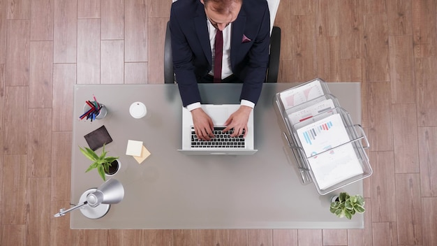 Bovenaanzicht van succesvolle zakenman in pak die marketingstrategie typt op laptop