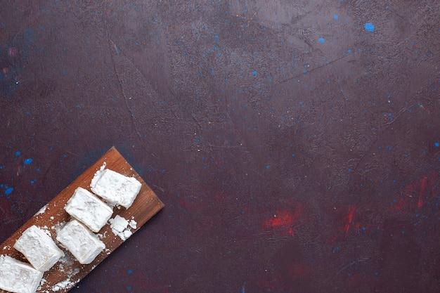 Bovenaanzicht van suiker poedersuiker nougat op het donkere oppervlak