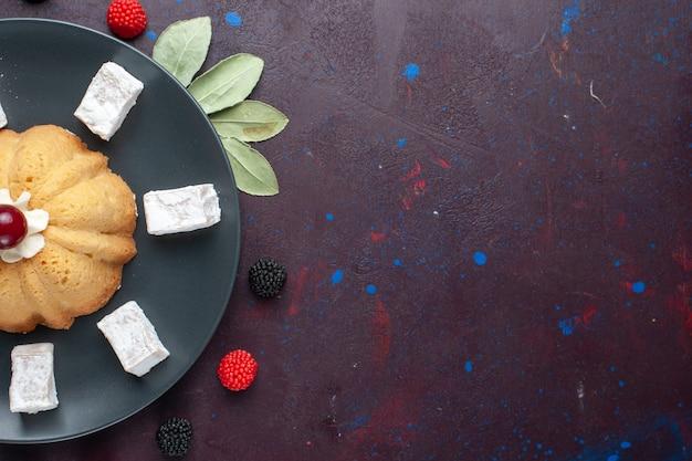 Bovenaanzicht van suiker poedersuiker snoepjes heerlijke nougat met cake en confituur bessen op donkere ondergrond