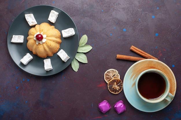 Bovenaanzicht van suiker poedersuiker snoepjes heerlijke nougat met cake in plaat op donkere ondergrond
