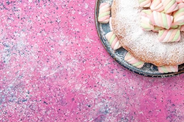 Bovenaanzicht van suiker poedertaart met zoete marshmallows op het roze oppervlak