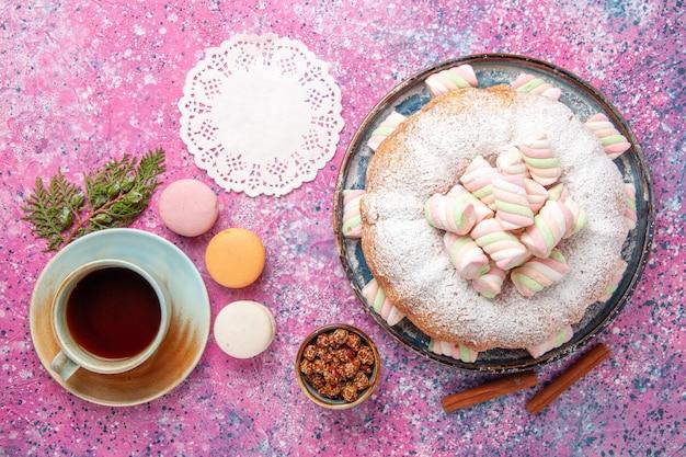 Bovenaanzicht van suiker poedervormige cake met kopje thee en franse macarons op roze bureau