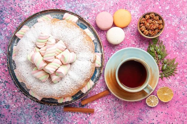 Bovenaanzicht van suiker poedervormige cake met kopje thee en franse macarons op roze oppervlak Gratis Foto
