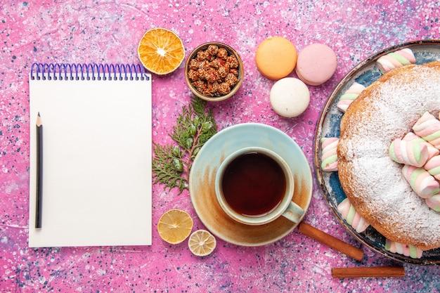 Bovenaanzicht van suiker poedervormige cake met kopje thee en franse macarons op roze oppervlak