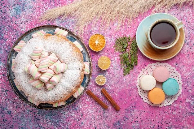 Bovenaanzicht van suiker poedervormige cake met kopje thee en macarons op roze oppervlak