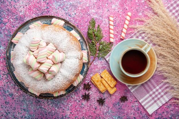 Bovenaanzicht van suiker poedervormige cake met kopje thee op licht roze oppervlak