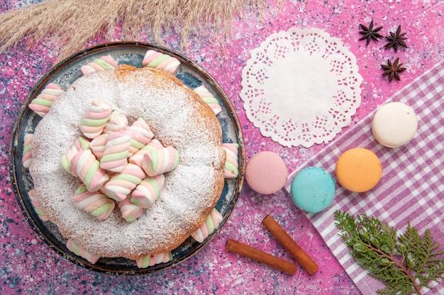 Bovenaanzicht van suiker poedervormige cake met macarons en marshmallow op roze oppervlak