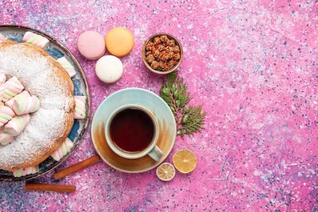 Bovenaanzicht van suiker poedervormige cake met thee en franse macarons op roze oppervlak