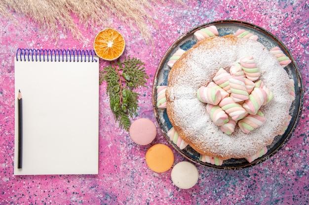 Bovenaanzicht van suiker poedervormige cake met zoete marshmallows en kladblok op roze oppervlak