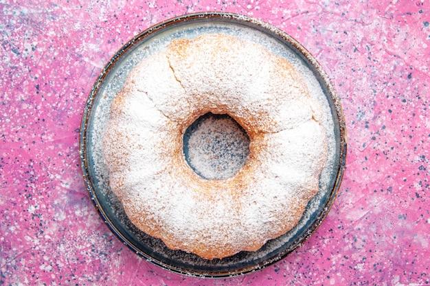 Bovenaanzicht van suiker poedervormige cake ronde gevormd op roze oppervlak