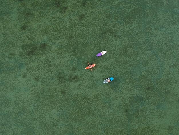 Bovenaanzicht van sup boards en kajaks op ondiep turkoois water van de zee van azov, oekraïne