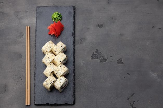 Bovenaanzicht van sushi roll met sesam op donkere grijze achtergrond Premium Foto