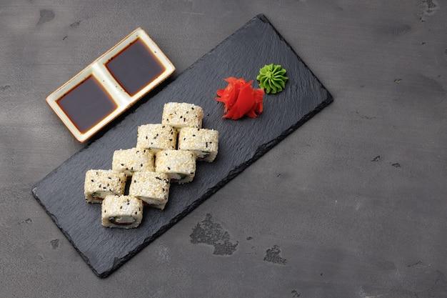 Bovenaanzicht van sushi roll met sesam op donkergrijs oppervlak Premium Foto