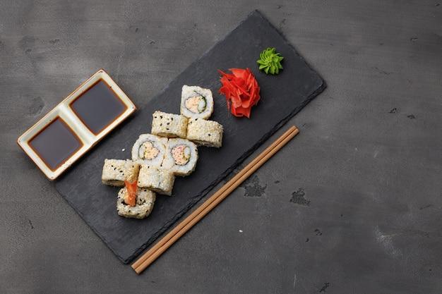 Bovenaanzicht van sushi roll met sesam op donkergrijs