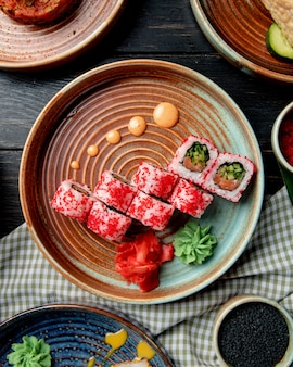 Bovenaanzicht van sushi roll met zalm, avocado, komkommer en roomkaas bedekt met rode kaviaar met gember en wasabi op een bord op houten tafel