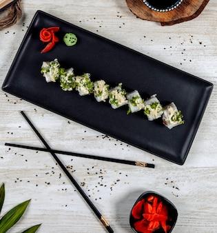 Bovenaanzicht van sushi rollen gegarneerd met kruiden en geraspte kaas