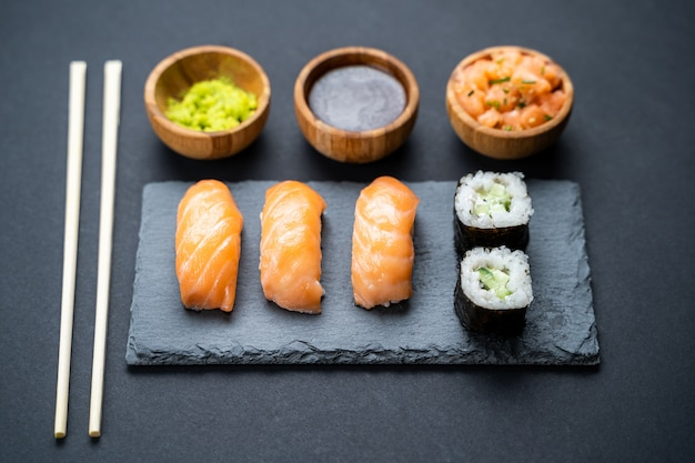 Bovenaanzicht van sushi rollen, maki, uramaki, nigiri en sashimi set geserveerd op stenen leisteen.