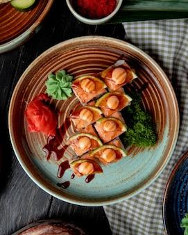 Bovenaanzicht van sushi rolt met garnalen avocado en roomkaas geserveerd met gember en wasabi op een plaat op hout