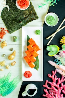 Bovenaanzicht van sushi set rollen met krab vlees roomkaas en avocado in kaviaar van vliegende vis met sojasaus op bamboe blad