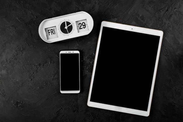 Bovenaanzicht van tablet en telefoon op effen achtergrond