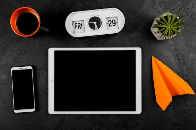 Bovenaanzicht van tablet klok en papier vliegtuig en koffiemok