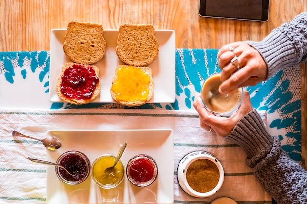 Bovenaanzicht van tafel met gezond voedsel en volwassen vrouw die ontbijt doet