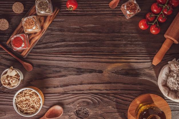 Bovenaanzicht van tafel met tomaat, champigons, aardappelsticks, ingrediënten en ruimte voor pizza-applicatie.