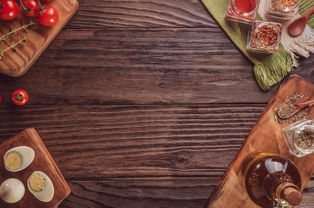 Bovenaanzicht van tafel met tomaat, gekookte eieren, olijfolie, oregano en ingrediënten met ruimte voor pizza-applicatie.