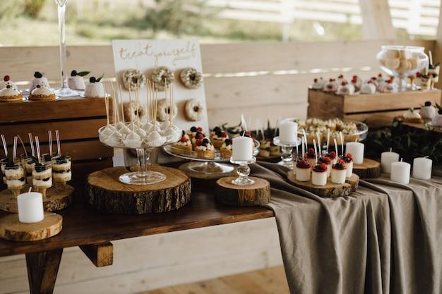 Bovenaanzicht van tafel vol met zoete heerlijke desserts, cupcakes, donuts en panna cotta desserts, snoepjes en tiramisu