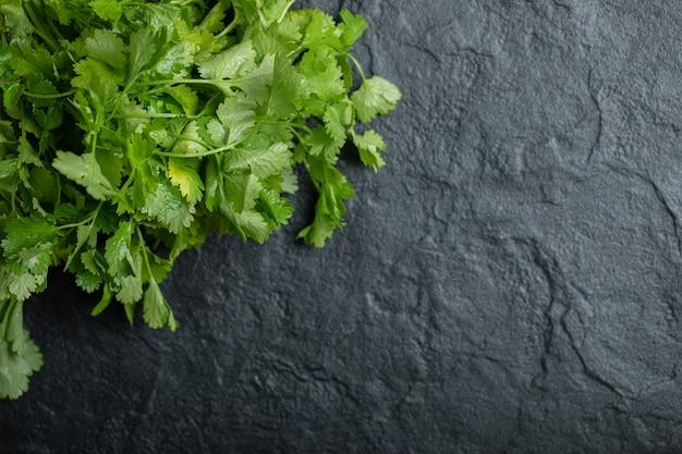 Bovenaanzicht van tak van verse koriander op zwarte achtergrond