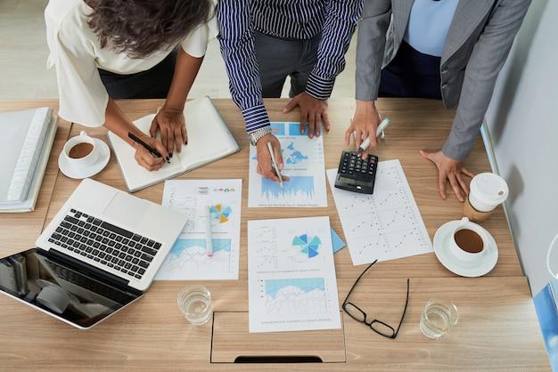 Bovenaanzicht van team van mensen die werken met documenten die inkomsten berekenen