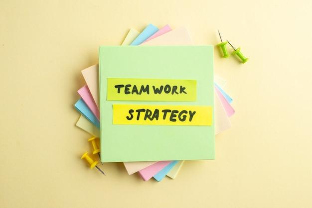 Bovenaanzicht van teamwork strategie schrijven op een van de gestapelde notitieblokjes op een gearceerde gele achtergrond met vrije ruimte