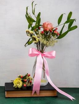 Bovenaanzicht van tedere en mooie bloemen met bladeren op een glazen vaas op witte ondergrond