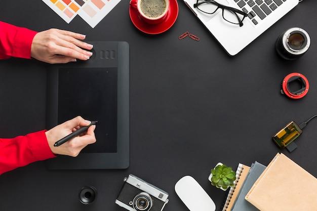 Bovenaanzicht van tekenblok met handen op het bureau
