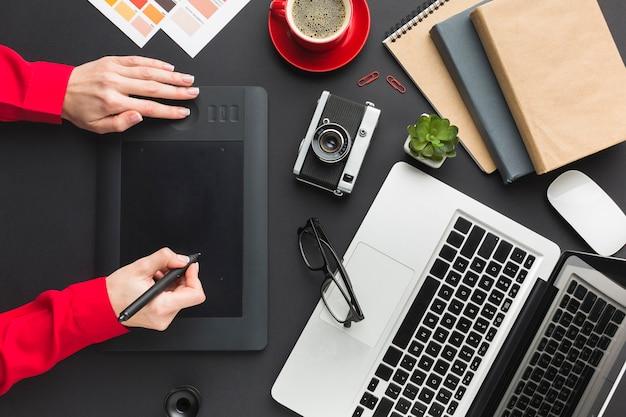Bovenaanzicht van tekenblok op bureau met laptop