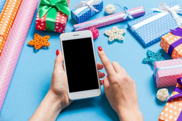 Bovenaanzicht van telefoon in vrouwelijke hand op feestelijke blauw
