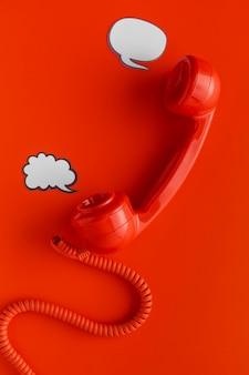 Bovenaanzicht van telefoonontvanger met praatjebellen en koord