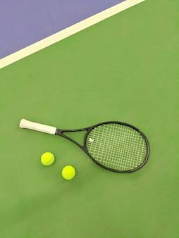 Bovenaanzicht van tennisracket en twee ballen op de tennisbaan van groene klei.