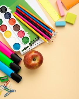 Bovenaanzicht van terug naar school briefpapier met appel en kleurrijke potloden