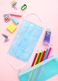 Bovenaanzicht van terug naar school briefpapier met kleurrijke potloden en medische masker