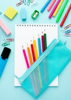 Bovenaanzicht van terug naar school briefpapier met kleurrijke potloden en notebooks