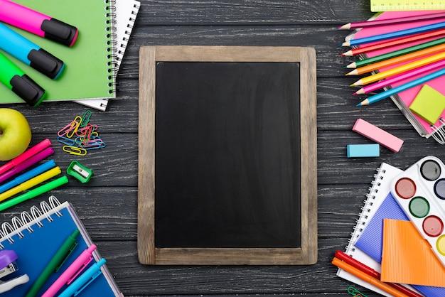 Bovenaanzicht van terug naar school briefpapier met kleurrijke potloden en schoolbord
