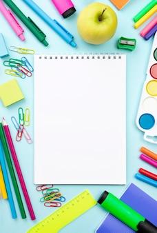 Bovenaanzicht van terug naar school briefpapier met laptop en appel