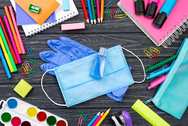 Bovenaanzicht van terug naar school briefpapier met medische masker en veelkleurige potloden