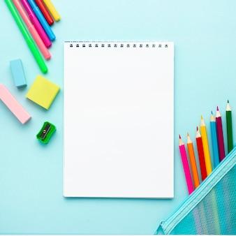 Bovenaanzicht van terug naar school briefpapier met notebook en potloden